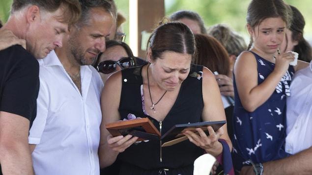Une femme en pleurs regarde les photos de ses fillettes.