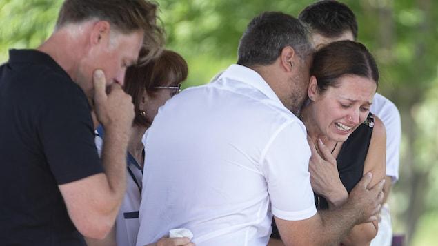 Une femme en pleurs consolée par des proches.