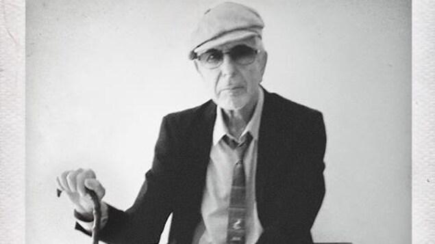 L'homme porte une casquette et se tient assis avec une canne.