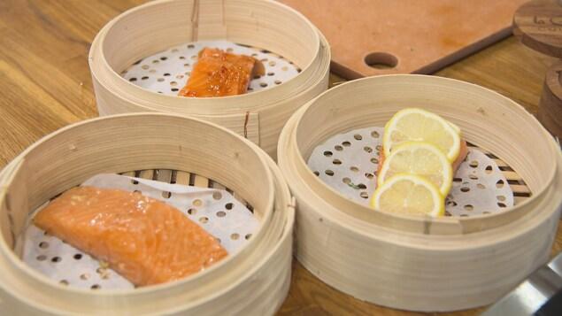 Trois paniers vapeur contenant des recettes différents de saumon.