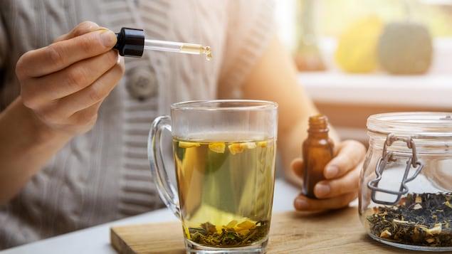 Une femme met de l'huile de cannabis à l'aide d'une pipette dans un thé.