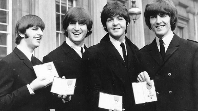 Les quatre artistes côte à côte sourient en montrant leur décoration