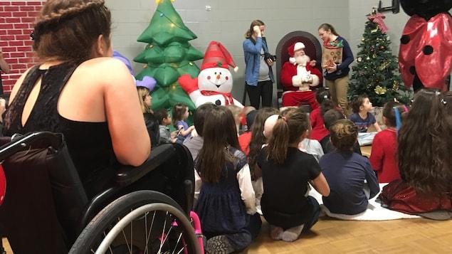 Le père Noël est assis sur une chaise devant des enfants