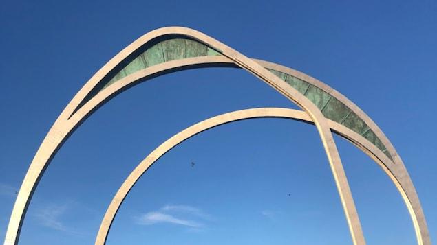 Des arches en métal sur fond de ciel bleu.