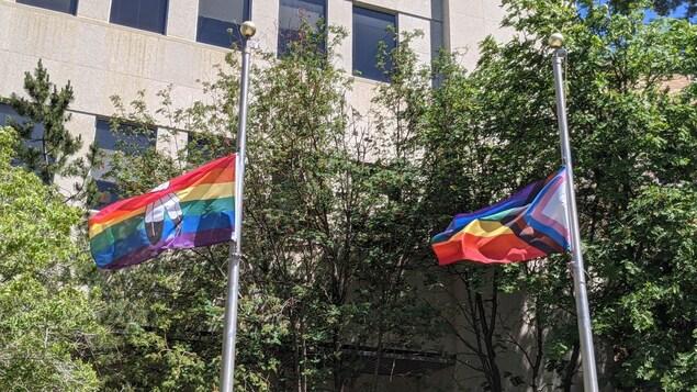 Deux drapeaux LGBTQ+ volent au vent.