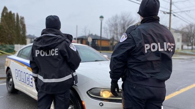 Deux policiers debout, de dos, devant leur véhicule dans un quartier résidentiel.