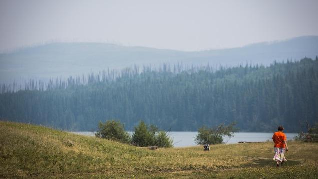Une personne marche près d'un lac.