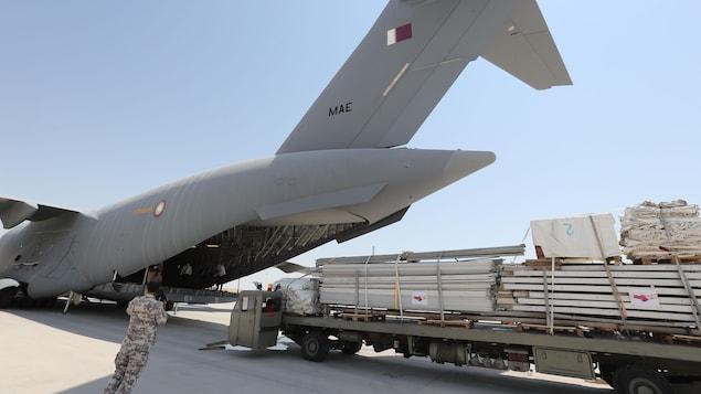 Des travailleurs chargent du matériel à bord d'un avion qatari.