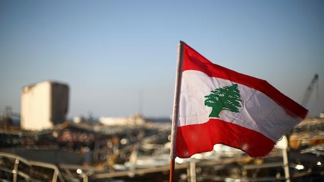 Le drapeau libanais flotte près de ruines dans le port.
