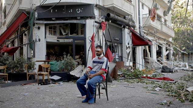 Un homme blessé est assis à côté d'un restaurant dans le quartier de Mar Mikhael à Beyrouth au lendemain de l'explosion.