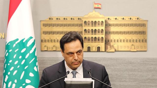Un homme devant un lutrin, tenant un dossier dans les mains. Il y a derrière lui un drapeau du Liban et une représentation du palais gouvernemental.