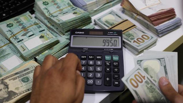 Une calculatrice affichant le nombre « 9950 », à côtés de plusieurs paquets de billets de banque.