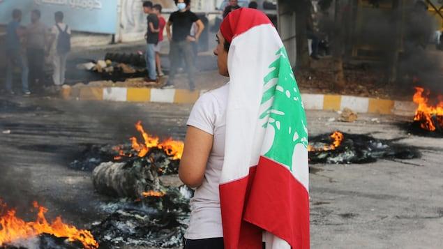 Une manifestante observe la situation, un drapeau du Liban autour de la tête. Les restes de pneus en feu brûlent autour d'elle.