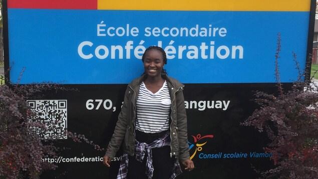 Photo de Liberasse devant le panneau de l'école