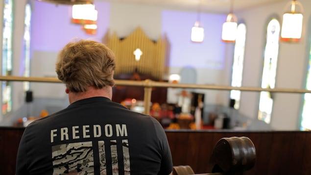 Un paroissien portant un t-shirt sur lequel on peut lire « Liberté » est assis dans le jubé d'une église.