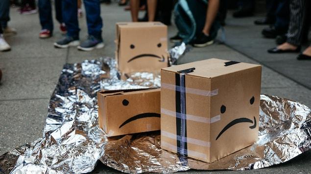 Des boîtes avec le logo d'Amazon trafiqué pour ressembler à des visages fâchés.