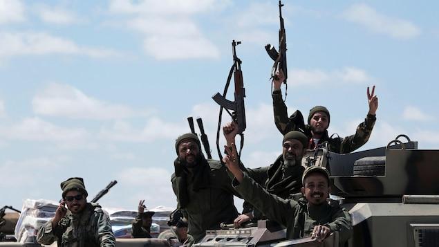 Des membres de l'Armée nationale libyenne font le signe de la victoire avec leurs doigts.