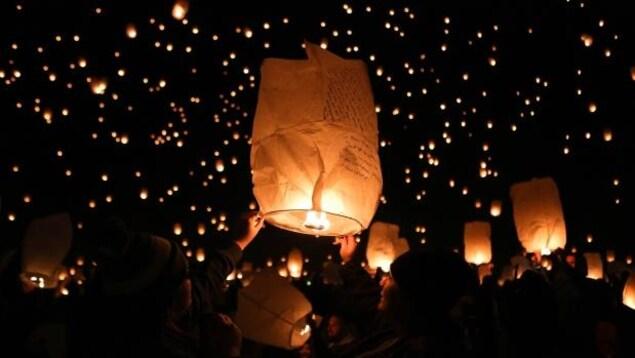 Des lanternes allumées avec du feux volent dans le ciel à la noirceur.