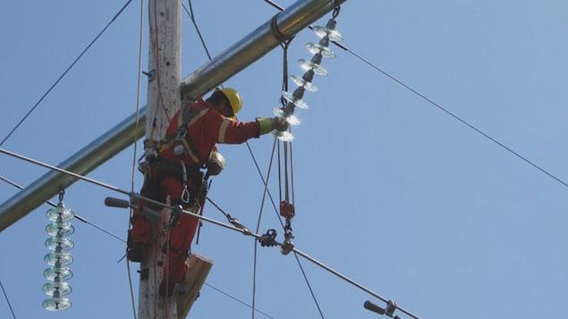 Un homme dans les airs en train de réparer une ligne électrique.