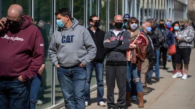 Des personnes font la queue à l'extérieur d'une clinique de vaccination.