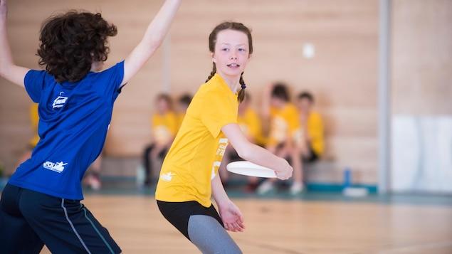 Une jeune fille lance un frisbee, un garçon tentant de la bloquer.