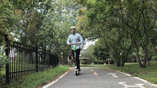 L'usager d'une trottinette électrique Lime sur une piste cyclable.