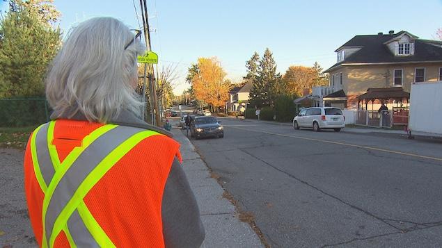 La directrice de l'école de dos avec un dossard orange et jaune qui fait la circulation devant son école.