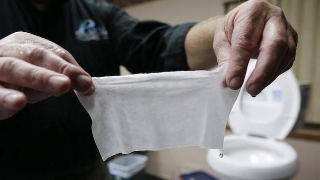 Des mains tiennent une lingette devant une cuvette de toilette.