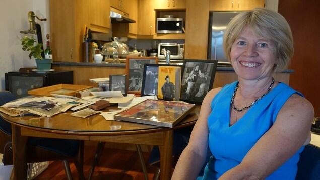 Une femme pose pour la caméra devant une table sur laquelle se trouvent plusieurs documents d'archives.