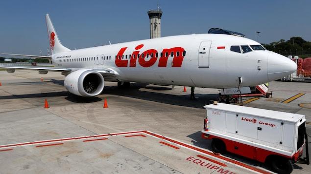 Les lettres rouges de la compagnie se dessinent sur le fond blanc de l'avion.