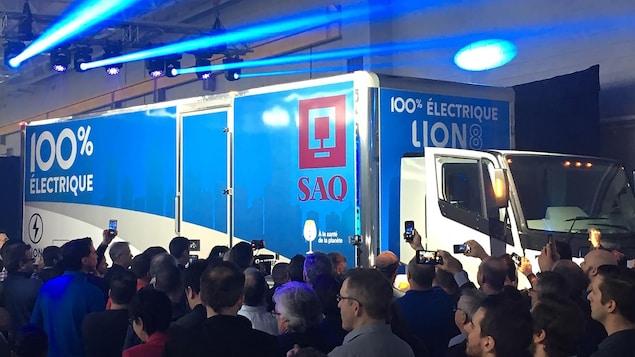 Les travailleurs de l'usine filment le dévoilement du camion avec leur téléphone.