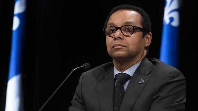 Lionel Carmant assis à la table de presse devant un drapeau du Québec affiche un air sérieux.