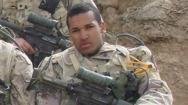 Lionel Desmond assis, en uniforme et avec son arme en Afghanistan.