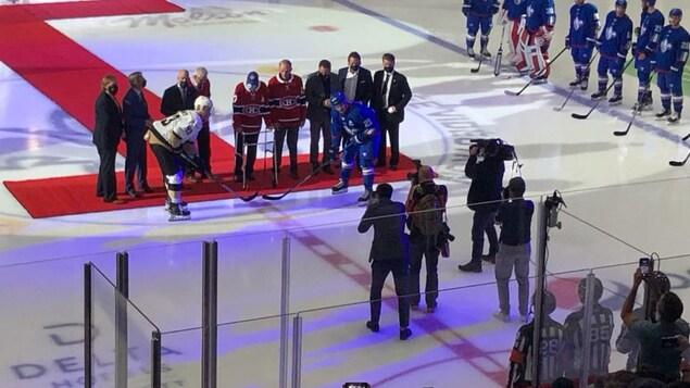Des joueurs et des dignitaires au centre de la glace pour la mise au jeu protocolaire.