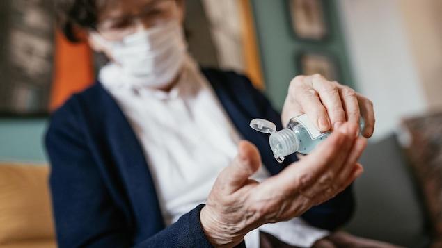 Une femme âgée verse du liquide désinfectant dans sa main.