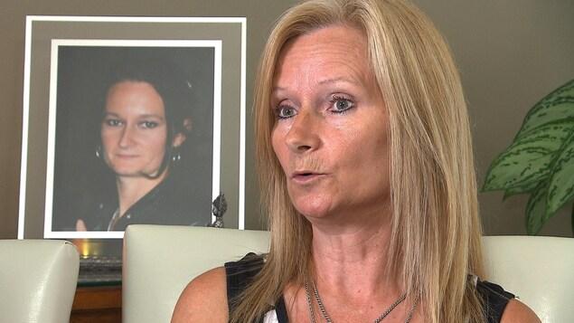 Lise Castonguay est assise sur une chaise blanche, devant une photo de sa fille Isabelle Lavoie, placée sur un meuble.