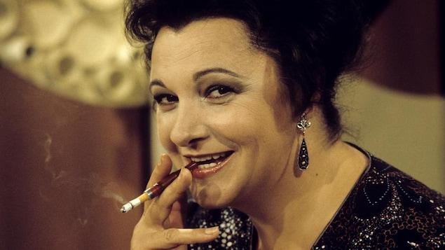 Dans un studio de télévision, l'animatrice Lise Payette est assise à son pupitre et tient un fume-cigarette contenant une cigarette allumée entre ses lèvres.