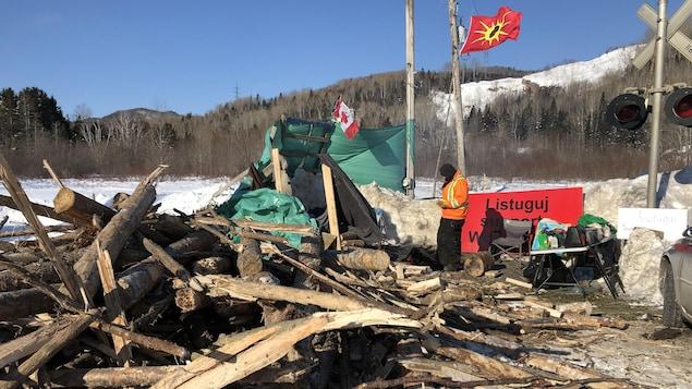 Un homme se tient devant un feu de camp protégé par une bâche. Tout près, des troncs d'arbre sont empilés sur le sol.
