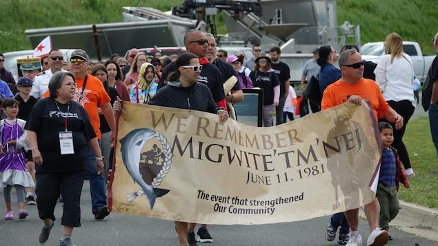 Des chefs autochtones tiennent une bannière lors d'une marche dans les rues de Listuguj.
