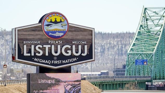 L'affiche de bienvenue à Listuguj et le pont interprovincial à l'arrière.