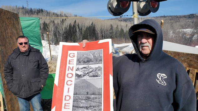 Un des militants venus du Nouveau-Brunswick présente une pancarte offerte aux gardiens de la barricade de Listuguj.