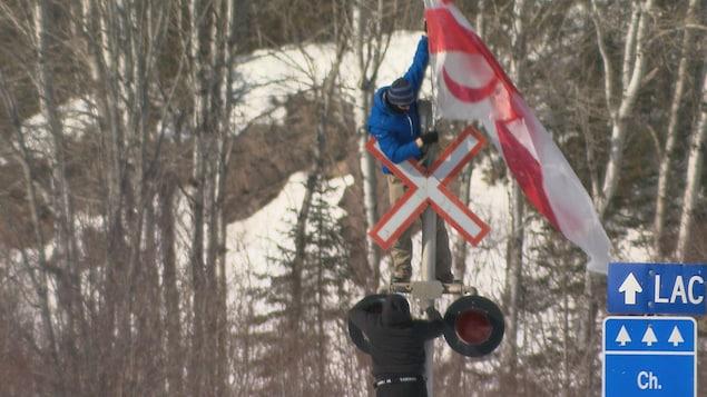 Un militant érige un drapeau de Listuguj au passage à niveau situé sur le territoire de la communauté.