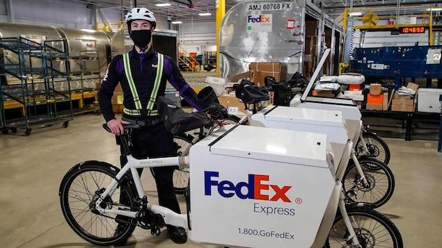 Un homme avec un masque et un casque tient un vélo de livraison dans un entrepôt