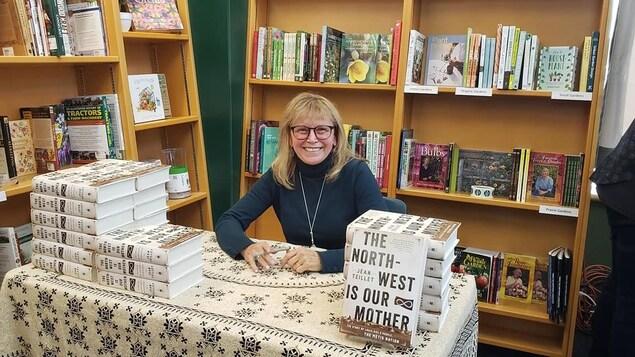 Jean Teillet est assis à une table sur laquelle est disposée son livre et sourit.