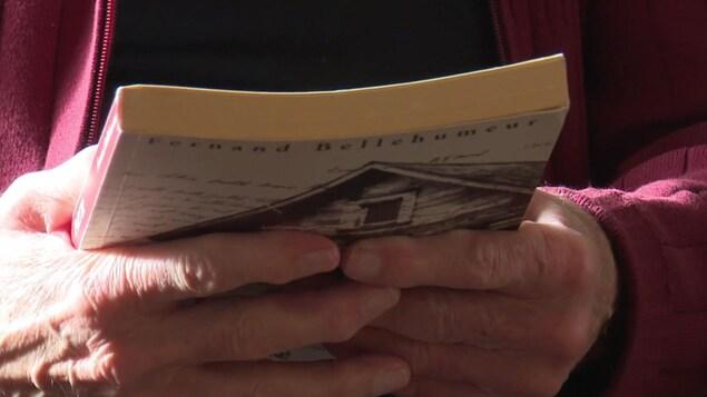 Gros plan sur les mains de Fernand Bellehumeur qui tient son livre «Partir».