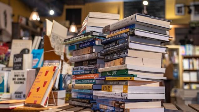 Une pile de livres d'auteurs locaux est posée sur une table dans la librairie.
