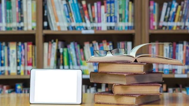 Sur un bureau, des livres sont posés à côté d'une tablette.
