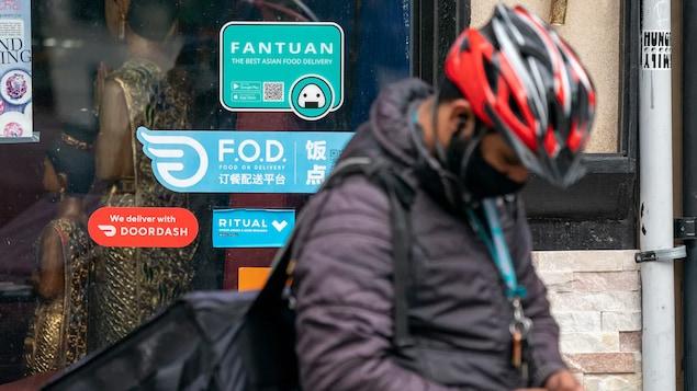 Un livreur consulte son téléphone devant la porte d'un restaurant.