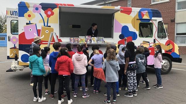 Un groupe d'élèves interagit avec un animateur qui se trouve dans le camion Livroooum.