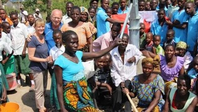 Claire et Marcel entouré d'habitants d'un village, rasssemblés autour du puit.